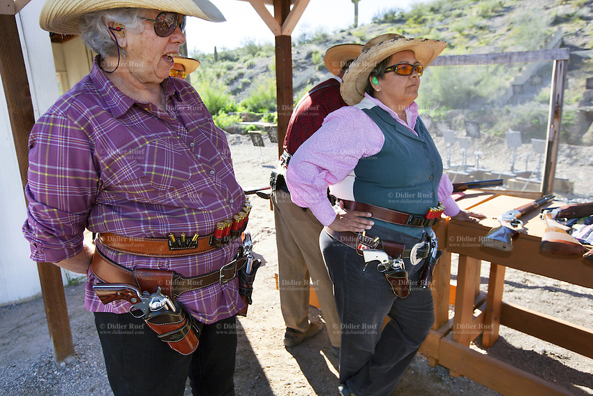 """USA. Arizona state. Peoria. Peoria is distant 50 km from Phoenix. Cowtown Shooting Range. Cowtown Cowboy Shooters Association. Fake town scenery from the old Far West time. A group of elderly men and women, all dressed with cowboys outfits, train outdoors for the incoming Winter Range - SASS National Championship of Cowboy Action Shooting ( february 22nd-28th, 2016). The Single Action Shooting Society (SASS) is a Cowboy Action Shooting (CAS, also known as Western Action Shooting, Single Action Shooting, or Cowboy 3-Gun). CAS is a type of multi-gun match utilizing a combination of pistol(s), rifle ( Winchester), and/or shotgun in a variety of """"old west themed"""" courses of fire for time and accuracy. Participants must dress in appropriate theme or era """"costume"""" as well as use gear and accessories as mandated by the respective sanctioning group rules. A CAS shooter engages a target with his lever-action rifle. Cowtown Shooting Range is a semi-private outdoor shooting range and firearms training facility. A firearm is a portable gun, being a barreled weapon that launches one or more projectiles often driven by the action of an explosive force. Most modern firearms have rifled barrels to impart spin to the projectile for improved flight stability. The word firearms usually is used in a sense restricted to small arms (weapons that can be carried by a single person). The right to keep and bear arms is a fundamental right protected in the United States by the Second Amendment of the Bill of Rights in the Constitution of the United States of America and in the state constitutions of Arizona and 43 other states. 31.01.16 © 2016 Didier Ruef"""