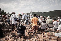 Faithful praying around the statue of the Virgin Mary, named locally as the 'Gospa' on the top of the Podbro, the hill of the apparitions. The exceptional heat wave (Charon) made temperature hit 41°C.<br /> Bijakovici, Medjugorje, Bosnia and Herzegovina.