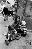 A Roma mother begs with her baby on a street corner in Przemysl on the Polish-Ukrainian border.