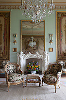A brightly coloured flower arrangement enlivens the white marble fire surround in the tapestry drawing room. Above, a large mirror reflects one of the framed tapestries that decorate the green walls