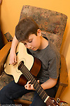 11 year old boy playing musical instrument guitar