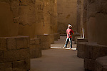 A male tourist wearing a red shirt and hat, stands in a beam of light among the stone pillars in the Great Hypostyle Hall in the Temples of Karnak, also known as the Amun Temple, on the East Bank of Luxor, along the Nile River, Egypt.