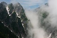 The jagged peaks of the Kaerazu no Ken mountains in the Hida Mountains, catching cloud. Nagano, Japan.