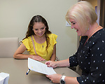 Paulina Zamarripa Miranda, left, gets the details of her scholarship from Board Member Jamie Gazza during the Nevada Women's Fund Scholarship distribution, June 20, 2019.
