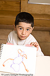 Education preschoool children ages 3-5 art artivity boy holding up his drawing of a human figure vertical