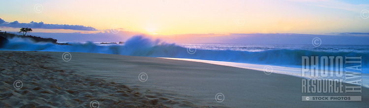 Panoramic shot of wave breaking on at Waimea bay on the North Shore of Oahu. Sun setting in the background.