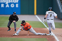 Norfolk Tides first baseman Ryan Ripken (11) stretches for a throw as Mikie Mahtook (8) of the Charlotte Knights hustle down the line while first base umpire Alex Tosi looks on at Truist Field on May 14, 2021 in Charlotte, North Carolina. (Brian Westerholt/Four Seam Images)