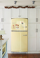 A vintage-style fridge is built into a wall of kitchen cupboards