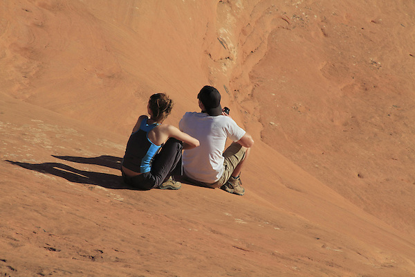 Couple sitting on slickrock at Arches National Park, Moab, Utah, USA. .  John offers private photo tours in Arches National Park and throughout Utah and Colorado. Year-round.