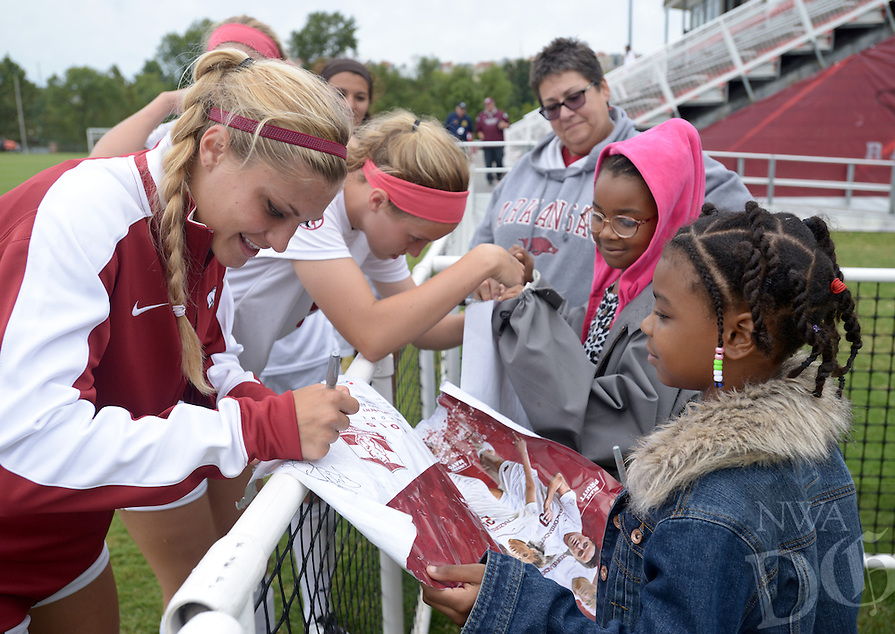 NWA Democrat-Gazette/BEN GOFF @NWABENGOFF<br /> Brianna Curtis (from left) and Rachel VanFossen of the Arkansas women's soccer team autograph posters for Autumn Williams, 8, and sister Amber Williams, 7, of Bentonville on Sunday Sept. 20, 2015 after the Razorbacks' loss to Mississippi State in Fayetteville.