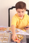 Ten year old boy working with Pokemon card collection, sorting them