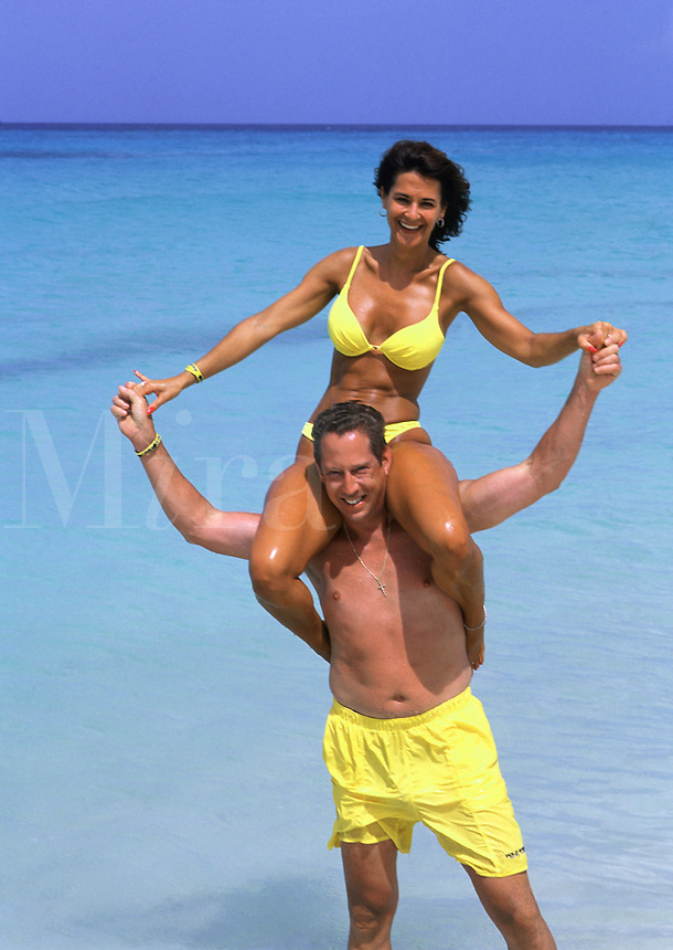 Couple in yellow swimsuits playing at beach