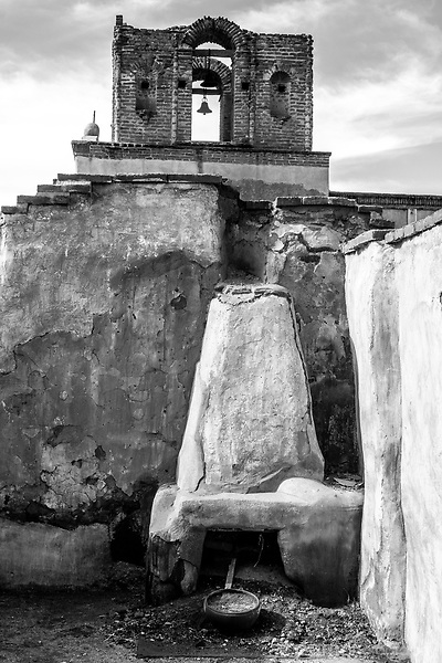 Black and white image of mission church bell with old mission fireplace