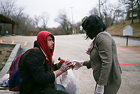 Monique Jones (right) offers food to Lloyd Koerter, Saturday, February 6, 2021 at the St. James Church in Fayetteville. Jones runs the food pantry there. She's turned the food pantry into a huge effort that collaborates with other area food banks as well as other NWA churches to deliver to 11 different communities in the NWA area. Check out nwaonline.com/210207Daily/ for today's photo gallery. <br /> (NWA Democrat-Gazette/Charlie Kaijo)