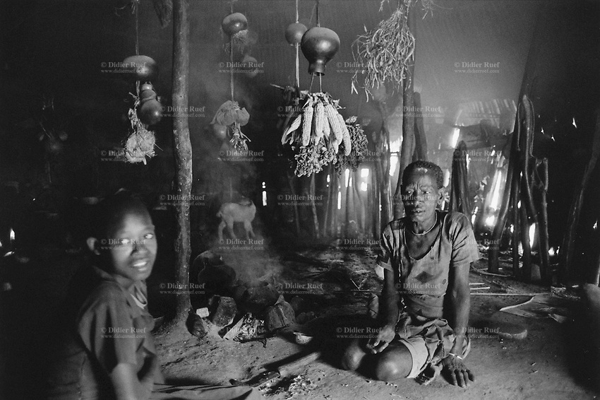 """Ethiopia. South Omo Zone. Salamago district. Gerfa (little village in the mountains).Inside a """"tukul"""" (hut) where a dime family (grand mother and a child) lives. Dime tribe lives in the mountains area. Permanently settled unless driven from their land by unsuspected attack of the neighbouring tribes Bodi and Mursi. The Dime tribe is located in the Debub Omo Zone (South Omo Zone) of the Southern Nations, Nationalities and Peoples's région. © 2001 Didier Ruef"""