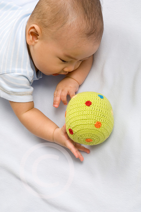 4 month old baby boy Chinese American closeup reaching for toy cloth ball vertical palmar grasp