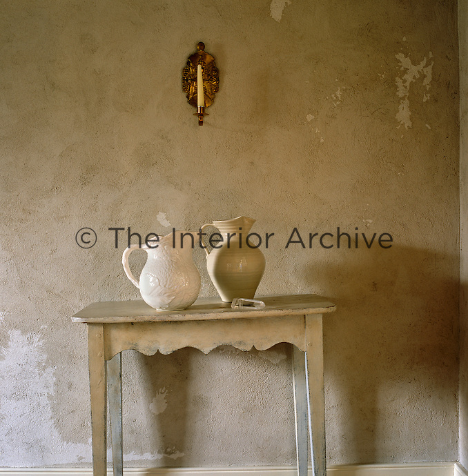 A sconce hangs on a mottled wall above a simple table with two ceramic jugs