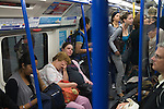 London Underground passengers. Pregnant woman tired and exhausted. UK