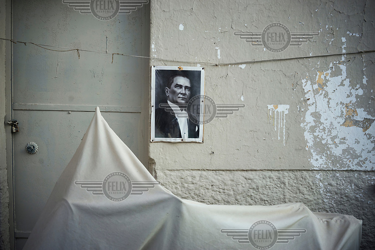 A poster of the Mustafa Kemal Ataturk pinned to the wall beside the door of a house.