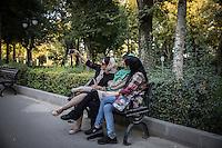 young people, ragazze velate sedate su una panchina si fanno un selfie