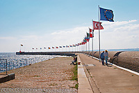 The Pier on Parapeten in the harbour. A long row of national flags flying in the wind. Two people walking. Blue sky. Helsingborg, Skane, Scania. Sweden, Europe.