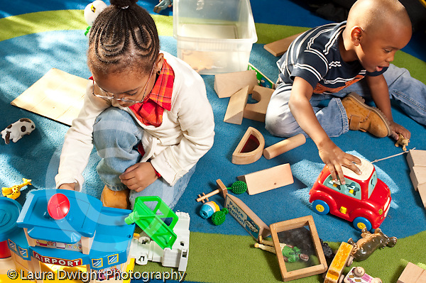 Education preschool 3-4 year olds boy and girl playing separately with plastic toy airport and vehicle horizontal