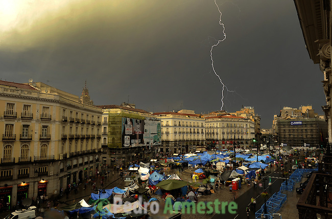 """A lightning falls on Madrid close to Puerta del Sol square on June 5, 2011 during a protest to decry mainstream political parties, soaring unemployment, corruption and welfare cuts. The leading protest group known as """"the indignants"""" met today to decide whether to carry on their camp-out against political corruption and joblessness. (c) PEDRO ARMESTRE"""