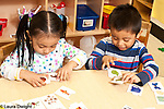 Education Preschool 3 year olds boy and girl playing separately with picture matching cards