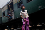 Alamgir standing by the railway track dazed by drugs with his sack. Its now when he will railway track to pick up plastic bottles which he will sell to buy for drugs. He is staying at Sealdah railway station for last 6 years from the time he ran away from his home due to domestic violence and poverty. As per his version his father was a drunkard and used to beat his mother for no reason. His father even could not earn enough money to buy food for their big family. Due to this traumatic situation he ran away from house at the age of seven. Ever since, the Sealdah railway station in Kolkata has been his home. As far as company is concerned, he had not much reason to miss his family. There are around 500 children, from 5 to 16 years, who live in the premises of Kolkata's second largest train terminus. Most of them addicted to Brown Sugar and sniffing industrial adhesive Dendrite. They say they don't feel hungry if they take the drugs. Their presence is conspicuous, even in a place that registers an average footfall of 1.4 million on weekdays. Their activities cover a wide range, from begging, to pulling handcarts, to petty theft, to selling odds and ends on the platform or on trains. The money, earned or ill-gotten as the case may be, is spent in procuring heroin, brown sugar, cocaine, and tubes of Dendrite. Calcutta, West Bengal, India. Arindam Mukherjee