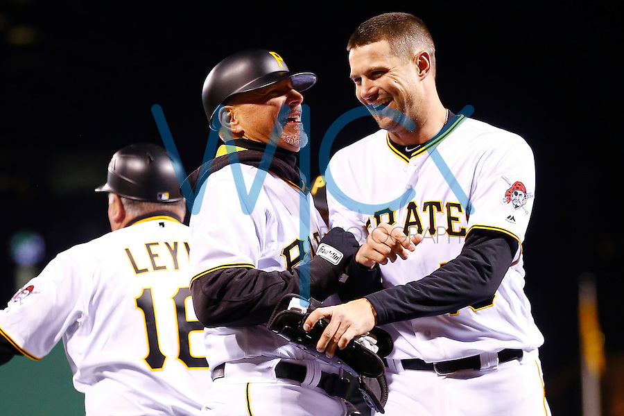 Jordy Mercer #10 of the Pittsburgh Pirates is congratulated by Rick Sofield #41 of the Pittsburgh Pirates following his walk-off hit in the 11th inning against the St. Louis Cardinals during the game at PNC Park in Pittsburgh, Pennsylvania on April 5, 2016. (Photo by Jared Wickerham / DKPS)
