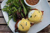 Eggs benedict served with potato waffles and hollandaise sauce, salad, and baked beans.