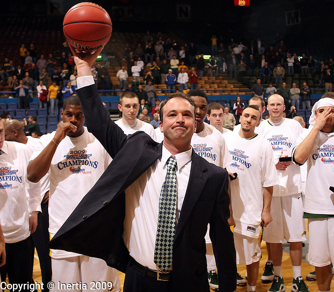 SIOUX FALLS, SD - MARCH 10: Head coach Saul Phillips of NDSU hoist the game ball following the Bison's 66-64 victory over the Oakland Golden Grizzlies in the Summit League Championship game Tuesday night at the Sioux Falls Arena. (Photo by Dave Eggen/Inertia)