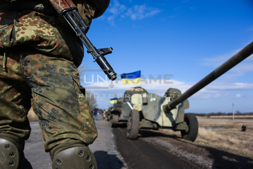 """Ukrainian soldier stands on guard with 100 mm cannons """"Rapira"""" at the background, while preparing for departure of the convoy during the withdrawal of heavy weapons. Near Artemovsk, Eastern Ukraine. Friday, 27 February 2015."""