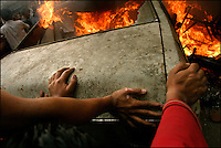 Anti-monarchy protesters set a car on fire, blocking the road in Kathmandu, Nepal on 20 April, 2004. Weeks of clashes between police and protesters calling on the king to reinstate democracy lead to thousands of arrests and hundreds injured.<br />