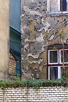 """UNGARN, 04.2009.Budapest - VII. Bezirk .Reste der Ghettomauer (Judenvernichtung 1944/45) im  alten Juedischen Viertel der Elisabethstadt (Erzs?betv?ros):  Die Mauer auf dem Hinterhof der Kertesz utca 18 riegelte das Haus hinten ab (Akacfa utca 25). Im Original scheint sie nicht mehr zu existieren, gut sichtbar sind aber Einschussloecher heftiger Kaempfe. Die Ghettogrenze verlief in Budapest nicht entlang von Strassen, sondern wurde hinter den Haeusern ueber Brandwaende und entsprechend verstaerkte Hofmauern gefuehrt, was Aufwand und Sichtbarkeit minimierte..Remains of the Ghetto wall (Holocaust 1944/45) in the old Jewish quarter of the """"Elizabethtown"""" district: The wall in the backyard of Kertesz street 18 cut off the adjacent house behind (Akacfa street 25). The original wall is probably gone, but shot holes after heavy fighting are clearly seen. The ghetto boundary in Budapest did not follow open streets, but was drawn behind the houses using party walls and reinforced courtyard walls, thus minimizing effort and visibility..© Martin Fej?r/EST&OST"""