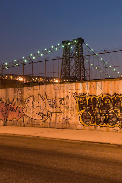 Williamsburg, Brooklyn, Cityscape at Dusk:....Street, sidewalk, wall with graffiti, Williamsburg Bridge in the distance, illuminated at dusk