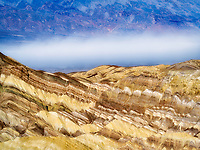 Colorful rock formations andf dust storm as seen from Golden Canyon Trail. Death Valley National Park, California