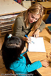 Education preschool 3-4 year olds female student teacher working with girl vertical talking and listening starting art nature activity