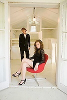 Man standing behind woman seated in red chair inside white house