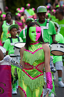 Woman marcher wearing vibrant green and pink face mask and dance outfit, Chinatown Seafair Parade 2015, Seattle, Washington State, WA, America, USA.
