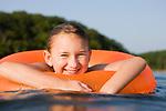 USA, Missouri, Stockton, Stockton Lake, girl (8-9) swimming in inflatable ring