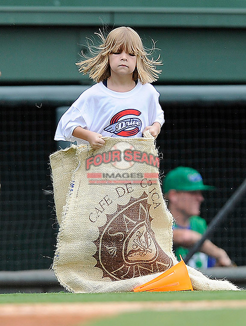 A young fan participates in the sack race between innings of a game between the Lexington Legends and the  Greenville Drive on Sunday, August 18, 2013, at Fluor Field at the West End in Greenville, South Carolina. Lexington won the first game of a doubleheader, 5-0. (Tom Priddy/Four Seam Images)