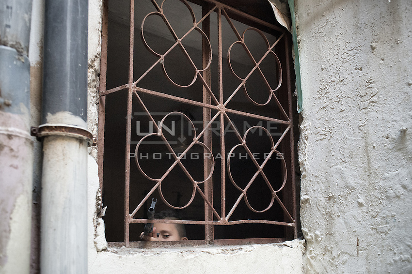 Kid looking outside his window protecting his home with a toy gun. In the shatila camp gun fights are frequent and kids are often imitating the scenes. Beirut. Lebanon. August 2015