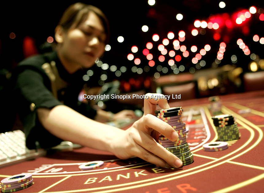 A dealer gathers in gaming chips at the newly opened 'Treasure Level' at the Sands Casino in Macao. By adding a further 273 gaming tables over more than 64,000 square feet of space on three floors, the casino owned and operated by the Las Vegas Sands Corporation today increased it's size by 58%. This increase makes it now largest casino in the world. The casino now accommodates a total of 740 gaming tables and 1,254 slot machines.
