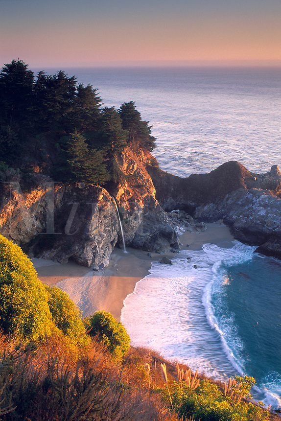 Sunset light over Pacific Ocean and waterfall, sand beach cove, crashing waves, and rugged coastal cliffs along the Big Sur Coast, Monterey County, California.