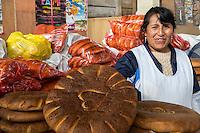 Peru, Cusco, San Pedro Market.  Woman Offering Bread for Sale.