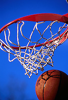 Graphic image of a basketball as it swishes through a net; high color contrast of hoop and sky.