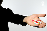 Man holding pills, close-up of hand (Licence this image exclusively with Getty: http://www.gettyimages.com/detail/sb10068346cb-001 )