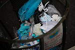 Surgical masks, gloves and other medical waste sit in a NYC garbage bin outside of Maimonides Medical Center on March 28, 2020 in Brooklyn, NY.  NYC's daily death toll from the coronavirus nearly tripled from the previous 24-hour period from 85 on Friday to 222 on Saturday.  Photograph by Michael Nagle/Redux