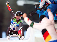 Germany's David Moeller celebrates winning the silver medal as his coach cheers his arrival in the men's singles luge at the XXI Olympic Winter Games Sunday February 14, 2010 at the Whistler Sliding Center in Whistler, British Columbia.